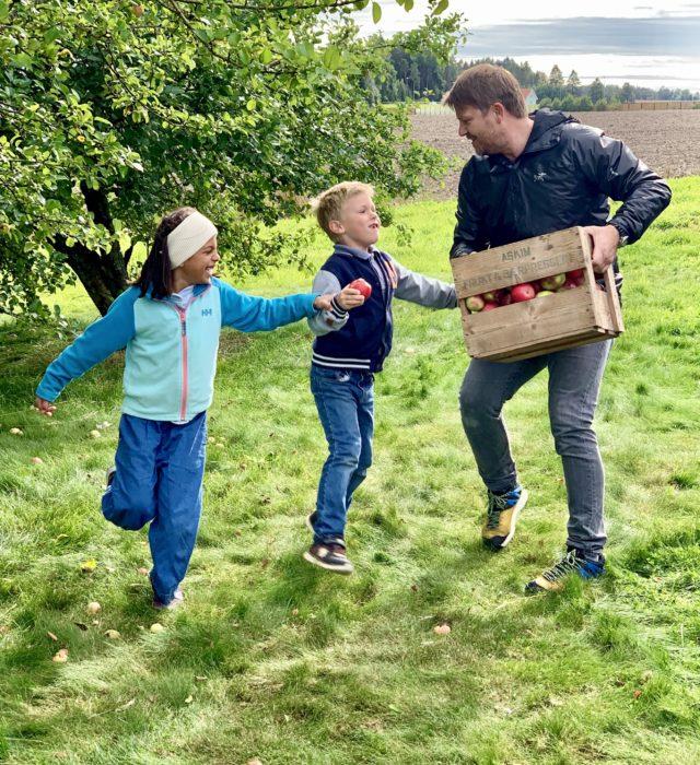 Nichlas og barna med eplekasse i hagen